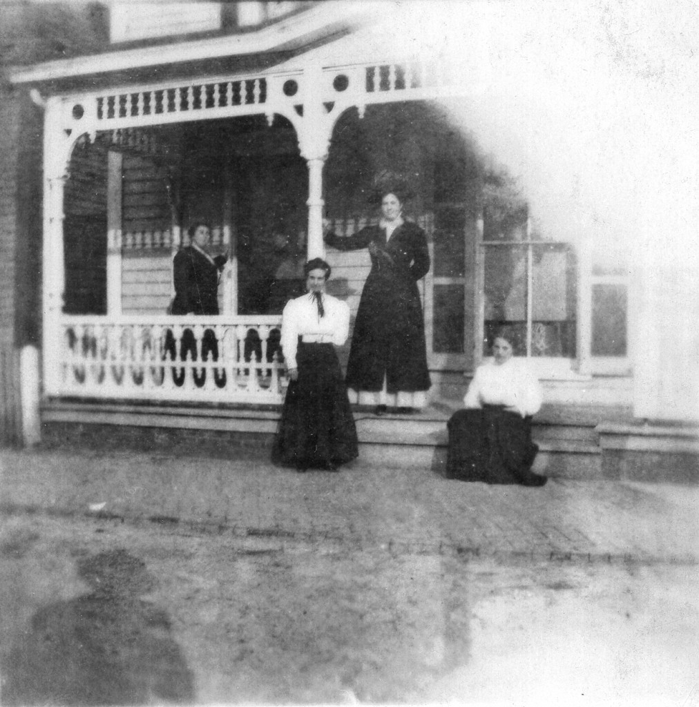 Photo of Lydia Ann Black in front of family home, seated at right.