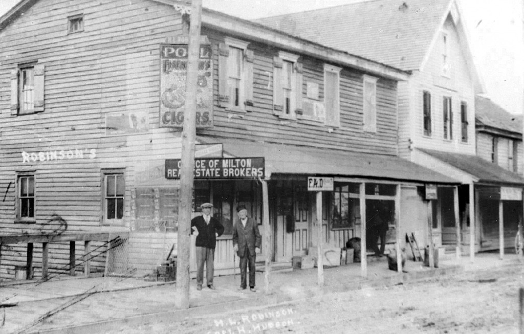 Estate office, Union Street, undated, including a a pool hall and real estate office. Capt. Henry Hudson is standing under the Choice of Milton Real Estate Brokers sign, at right.