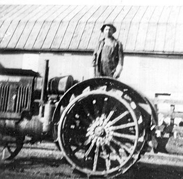 John S. Isaacs on early model gasoline-powered tractor, ca. 1930