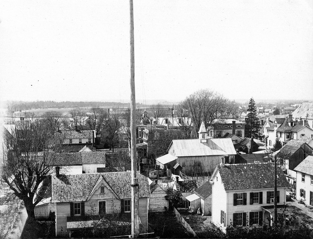 View from the school cupola over the front of the school, flagpole visible in foreground. Houses on Chestnut and Federal Streets are visible, but not the streets themselves. A portion of Wagamon's Pond is visible in the background.