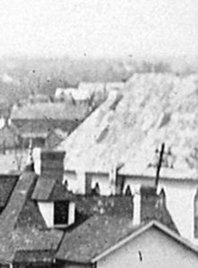 Detail showing roof, one wall and the tops of several Gothic Arch windows of St. John Baptist Church; note the absence of the brick façade from the wall.